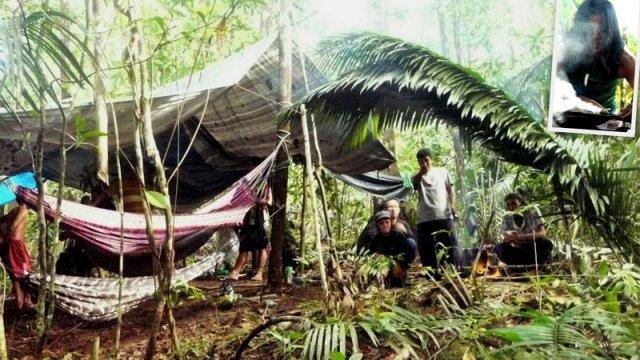 Das Urwaldcamp aus Hängematte unter einer Plane und ein Feuer unter ein paar Palmenblättern gegen Regen geschützt. Rechts oben wird der Rauch einer Wurzel als Schutz gegen Schlangen, Malaria und böse Geister genutzt.