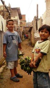 Zwei Jungs haben Bananen von einer Staude am Favelarand abgeschnitten und tragen sie nun in ihre Hütte um sie dort ausreifen zu lassen.