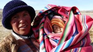 Eine Bäuerin vom Titicacasee mit ihrem Baby im Tragetuch, dass sie sonst auf dem Rücken trägt.